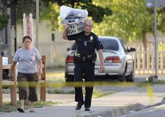 Aurora Police Officer Campagna carries a laundry basket for a resident that got to return for a few minutes to her home. Residents of neighboring apartments got to return to collect items from their homes that had been evacuated because of the bobby trapped home of shooting suspect James Holmes in Aurora on Friday, July 20, 2012. Cyrus McCrimmon, The Denver Post