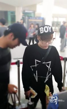 Sunggyu (Kim Sung-kyu), a South Korean singer-songwriter, musician, actor, MC, and vocalist from the band Infinite, is wearing a Long Clothing Enneagram Pocket Sweat and a Boy London Boy Snapback Black Cap.