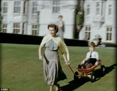 Royal roller: The Queen pulls a young Prince Charles down a grassy slope on a sunny day in the castle grounds
