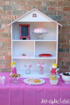 doll themed birthday party with dollhouse shelf as backdrop