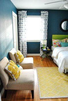 i just painted my bedroom a grayer shade of this deep of a blue...to me it looks like a boy room against our brown window and door frames (that will change to white very soon).  i love the color palate used here to brighten it up...i have to go shopping now :)
