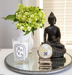 Diptyque candle, buddha and fresh flowers on a mirror