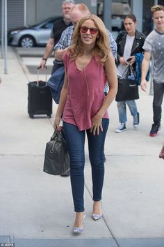 Life's rosy! Beautiful Kylie Minogue beams in blush pink camisole as she shows off her per...