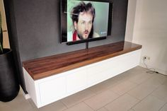 Hoogglans wit zwevend tv meubel 300 cm lang met hoogglans notenhouten blad. Bezoek onze website en maak een afspraak om een 3D ontwerp en offerte op te laten maken.