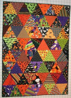 """Scrappy Halloween quilt by The Polka Dot Chicken.  2013 Bloggers' Quilt Festival. This quilt measures 50 X 68 and it has 88 different Halloween fabrics.  The triangles are 9"""" tall which was a nice size to show off the larger prints.  Made with a 60-degree ruler."""