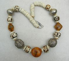 Necklace made up of 2 large antique round silver Yemeni beads  old, rare copal amber beads from Mauritania, 8 batik camel bone beads from Kenya, African mixed metal beads and African ostrich egg discs.