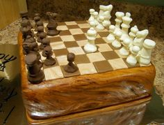 Chess Anyone? Chocolate cake with vanilla custard filling covered in fondant which was hand panted to look like wood. Chess pieces are made out of white and dark chocolate.