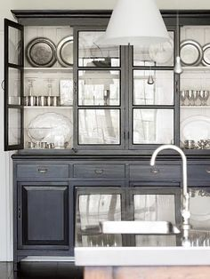 Dark china cabinet with light interior and glass doors.
