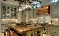 kitchen by Leslie Sinclair, owner of Segreto Finishes, rustic work table, island, copper vent hood, lanterns, glass-fronted cabinets, exposed beams