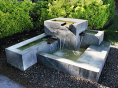 Fountain of rough concrete perfectly complement the modern garden