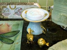 A footed dish elevates the mundane and frees up counter space to boot. Fashion a pedestal for your powder room out of a china plate and a short crystal candlestick. To give your soap a lift, flip a fancy teacup upside down and top it with the matching saucer.