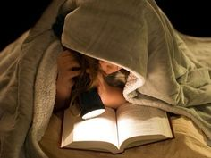 Children: A young girl reading a book under the covers with a flashlight