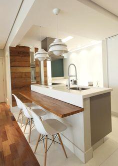 Cozinha aberta com ilha.  Bancada em  silestone e mesa em madeira de demolição. Piso porcelanato Portobello