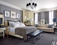 A chandelier by Williams-Sonoma Home overlooks the master bedroom; the folding screen and sofa are vintage, the herringbone wool blanket is by Ralph Lauren Home, and the velvet curtains are by Restoration Hardware.