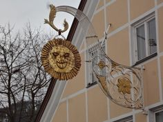 This is an old unique artistic shop sign for a restaurant called 'Gasthof zur Sonne' (Restaurant Sun). It is located in the 'Kemptener Straße' in Nesselwang, Germany, Bayern.