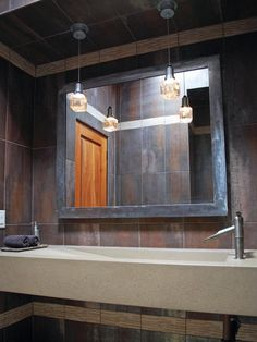 A narrow concrete sink spans the width of the wall in this earth-toned bathroom. Above, a steel framed mirror and small glass lights add an industrial feel to the space.