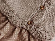 modèle tricoté du bas vers la haut et sans couture, bordé d'une bande de coquilles et boutonné sur le côté.