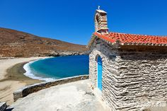 A small chapel in #Achla beach, #Andros island ~ Greece.  Everything is notable--texture, tile, seawall, blue door.  Try pulling that out of a big box store.