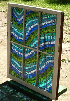 Take one salvaged old wooden window, add some stained glass and let light shine through. Hand cut stained glass, following a pattern, just the same as for a soldered panel. The glass is glued to the original glass and then grouted.