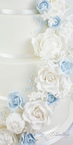 Cascading white and powder blue roses on a white wedding cake