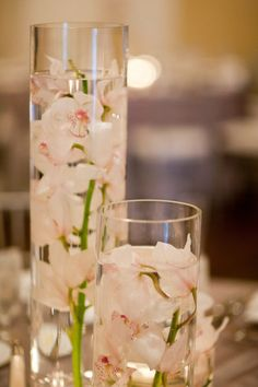 wedding white flowers / centrepieces  These could be nice with one with a candle in, maybe three of different heights per table