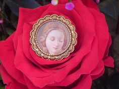 This elegant round gold-tone brooch enshrines an exquisite Renaissance-era depiction of the Virgin Mary with eyes downcast in reverent prayer.