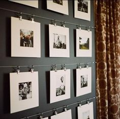 white matted photos hung from clips on wire with charcoal gray background