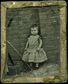 Outdoor portrait photograph of a little boy, Charles Cooper Savage, in a back yard. Charles was born on 11 June 1855. He wears a dress and is about 3 years old