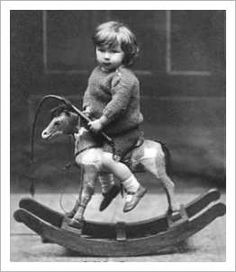 Little Boy on a Very Small Rocking Horse with a Whip in His Hand