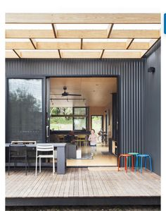 Contrast of light timber and black corrugated cladding. Pergola and big windows with a pop of colour added though