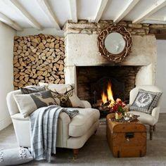 déco campagne chic dans le salon avec cheminée,coffre en bois et plafond en poutres