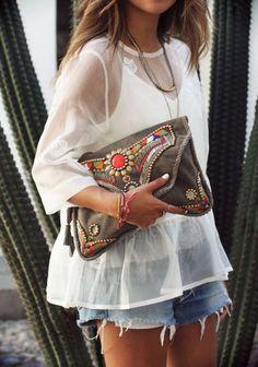 Une blouse blanche ample toute en transparence sur un petit short en jean (pour les beaux jours) et le tout rehaussé par une superbe pochette colorée ornée de pierres et de strass.