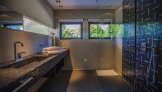 Nádherná tmavá mozaika s jemnou béžovou stěrkou a bodovým osvětlením vytváří ambivaletní atmosféru.