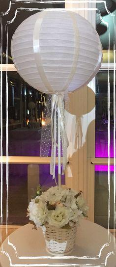 Centrotavola realizzato von cestino di vimini, fiori artificiali, nastri e lanterna di carta.