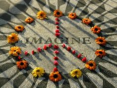 """A makeshift peace sign of flowers lies on top John Lennon's """"Strawberry Fields"""" memorial in New York's Central Park. Description from cognoscenti.wbur.org. I searched for this on bing.com/images"""