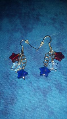 Perfect way to show your Patriotism or love of country. Silver tone alloy is used to create these fun earrings, Each is accented with red, clear & blue glass star beads. Each star is approx 11mm. Earrings hang approx 1.5 inches and closure is silver tone surgical steel hook with clear rubber stopper.