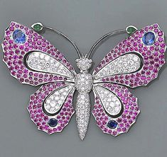 A gem-set and platinum butterfly brooch designed with a body pavé-set with round brilliant-cut diamonds, the wings pavé-set with round facet-cut rubies, accented by four bezel-set round and oval-shaped sapphires, with cabochon emerald antennae; estimated total diamond weight: 1.85 carats.