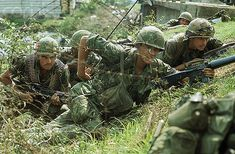 11 May 1968, Saigon, Vietnam --- 5/11/1968-Saigon, South Vietnam: Photo shows troops in a trench next to a bridge, with their machine guns, awaiting orders or action. --- Image by © Bettmann/CORBIS