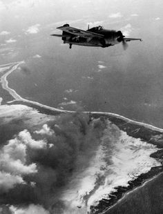 An FM-1 Wildcat flown by Lieutenant (junior grade) G.V. Knudson of Composite Squadron (VC) 41 flying from the escort carrier Corregidor (CVE 58) pictured over Makin Atoll on November 20, 1943, seventy years ago today. Smoke is visible from oil fires near Kings Wharf.
