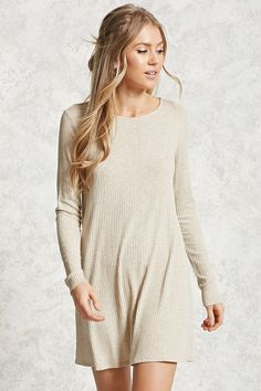 A ribbed knit mini dress featuring a shift silhouette, round neckline, long sleeves, and a vented hem.