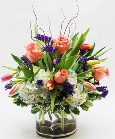 """"""" with this Impressive Arrangement Designed to make a Huge Statement for any Occasion. Filled with Beautiful Peach Roses, Dainty Tulips, Fluffy Blue & White hydrangea with a pop of color from Purple Status,. Get Well Flowers, Glass Cylinder Vases, Vase Arrangements, Mothers Day Flowers, Spring Has Sprung, Spring Flowers, Red Roses, Tulips, Color Pop"""