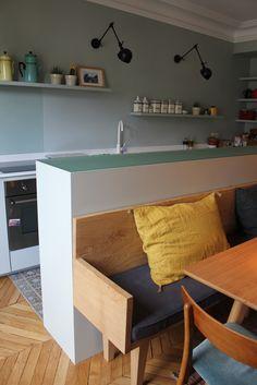 On aime cette idée qui change du plan bar classique de la cuisine américaine ! Ici, une série de meubles fait face au premier plan de travail. Plus hauts, ces meubles dissimulent la cuisine et servent de dossier au banc de la table à manger.