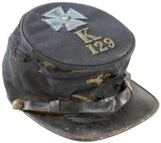 """Federal Forage Cap w/ V Corps Badge and Unit Insignia, worn by an unknown member of Co. K, 129th Pa. Vol. Infantry, a unit that saw nine-months service with the Army of the Potomac. The crown is decorated with a hand cut V Corps badge upon which is affixed a small stippled numeral """"5"""" and, in the center, a silver metal eagle. Below the badge is a 1"""" brass letter """"K"""" and ¾"""" numerals """"129."""" The cloth badge is blue in color of the 3rd division."""