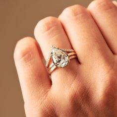 To last any and every season! Fresh and dewy, for a lifetime! We love the Summer Rain engagement ring for it's fresh-cut flora feel, romantic and girly and vivacious. A three carat, pear-shaped moissanite, clear and nearly colorless, stands out in a hammered golden halo setting, on a slim and gamine 1.5mm band of burnished yellow gold. And as the years go on, add shimmering details like a tiara diamond band and wedding ring! • ✨What do you think of pear shapes?✨ Pear Shapes, Pear Diamond Engagement Ring, Halo Setting, Summer Rain, Diamond Bands, Moissanite, Flora, Girly, Wedding Rings