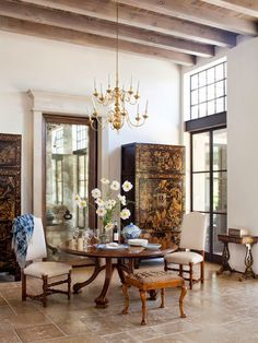 So much to like here: door framed as a mirror, chinoisserie chests, limestone tile floor, undressed windows