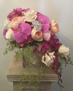 A cascading bridal bouquet with phalenopsis and dendrobium orchids, peach and pink garden roses, etc.