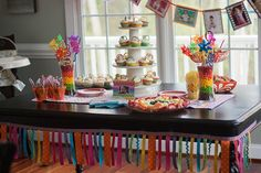 Our rainbow theme 1st birthday party for Scout -- rainbow cupcakes with twizzler rainbows on the icing, fruity pebbles krispie treats, skittles layers in vases, rainbow colored windmills from the dollar store, rainbow ribbon table trimmer, rainbow pennants with Scout's picture from each month, a rainbow fruit platter, and probably more I've forgotten to add!  And all inspired by Pinterest!