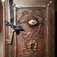 """Altered book, hand made fimo clay eye, card board, paper towel, paint, salvaged hardware, ribbon, etc. By smee"" --It almost looks like the book from Hocus Pocus!! Squee!"