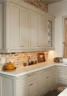 gray kitchen. gray kitchen cabinet with brick backsplash wall and
