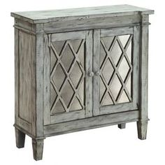 """Mirrored two-door cabinet with lattice panels and a weathered finish.  Product: CabinetConstruction Material: Wood and mirrored glassColor: Weathered greyFeatures:  Two doorsFixed interior shelf Dimensions: 34.25"""" H x 35.25"""" W x 12.5"""" D"""